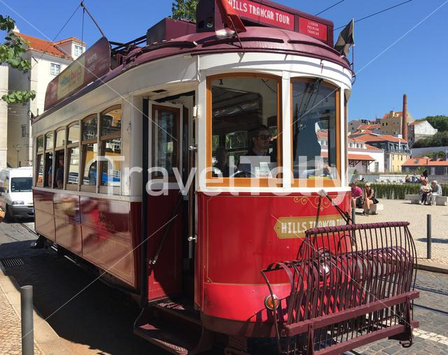 A red tram in front of Portas do Sol in Lisbon Portugal