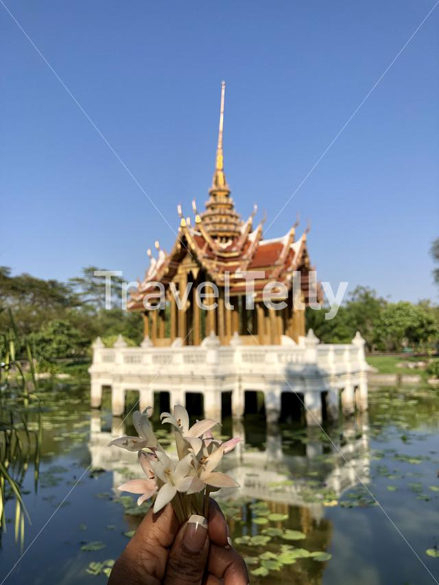 Flowers in a hand in front of a Thai temple building in a lake at King Rama IX Park in Bangkok, Thailand