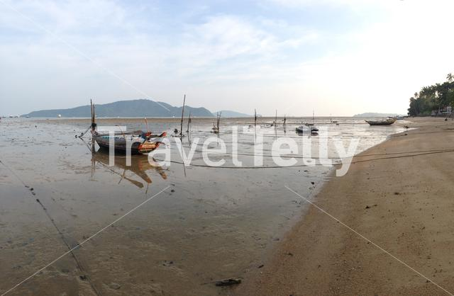 Boats on the beach with low tide in Phuket Thailand