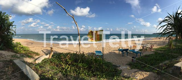 Panorama from Tangalle beach with Srilankan flag and beach chairs