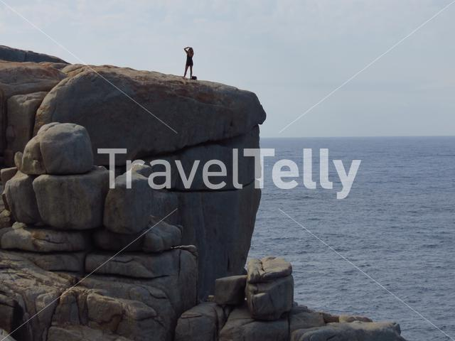 Girl photographing at the Gap a stone formation in Torndirrup National Park Albany Western Australia
