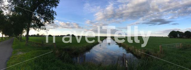 Road and farmland panorama landscape in Friesland The Netherlands