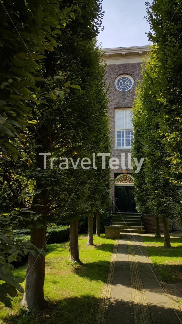 Old building behind trees next to prison in Enkhuizen