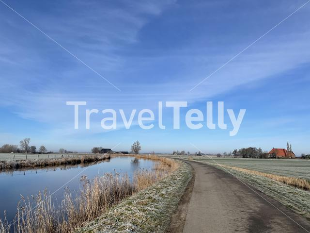 Road next to a canal around Aldeboarn during a winter day in Friesland The Netherlands