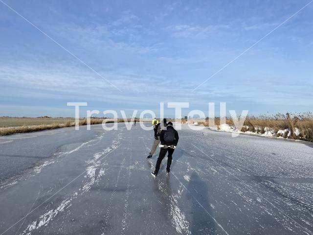 Ice skating on a frozen canal in Friesland The Netherlands
