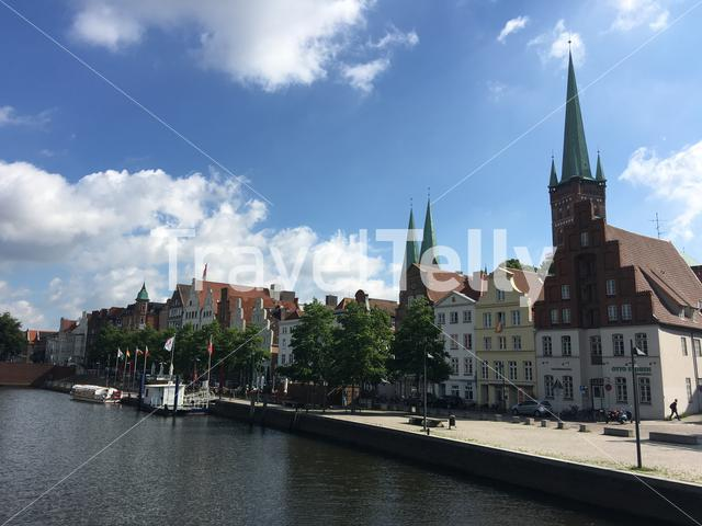Boats in the Trave river and houses in the old town of Lübeck Germany