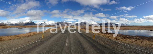 Panorama from an empty road with snowy mountains landscape in South East Iceland