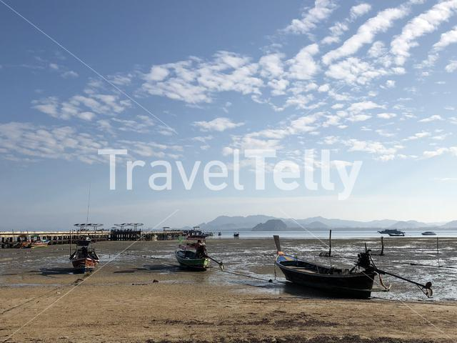 Long-tail boats during low tide in Koh Mook Thailand
