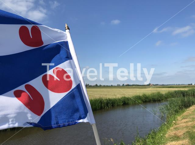 Frisian flag at the canal the Opfeart around Atzeburen in Friesland, The Netherlands