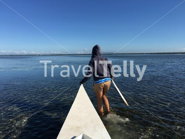 Girl walks with low tide in front of a Catamaran Boat in Panglao bay Bohol the Philippines
