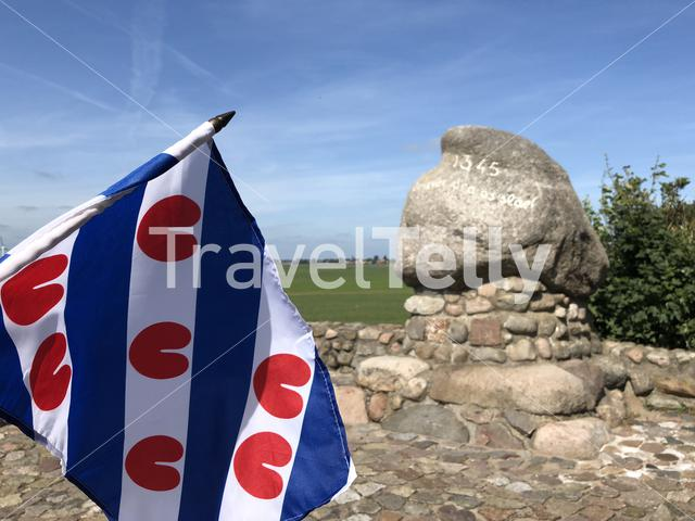 Frisian flag in front of the monument (Better to be dead than a slave) of the battle of Warns in Friesland, The Netherlands