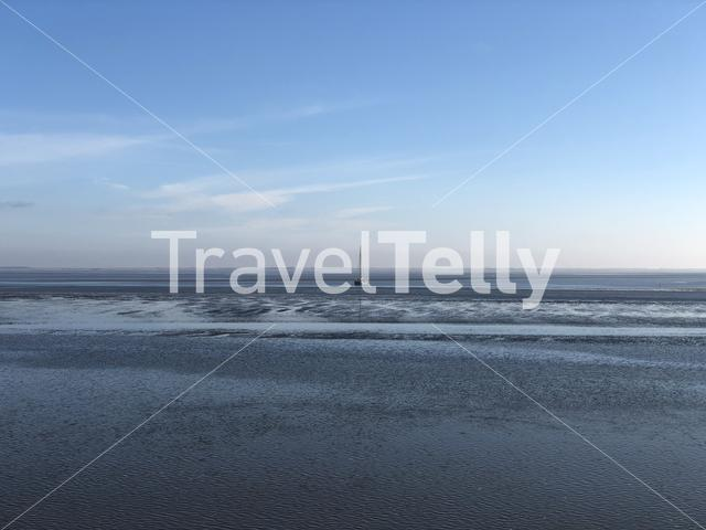 The Wadden Sea during low tide with a sailboat in Friesland The Netherlands