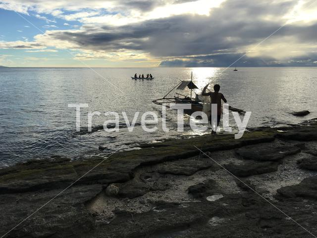 Fisherman silhouette during sunset at Balicasag Island in Bohol the Philippines