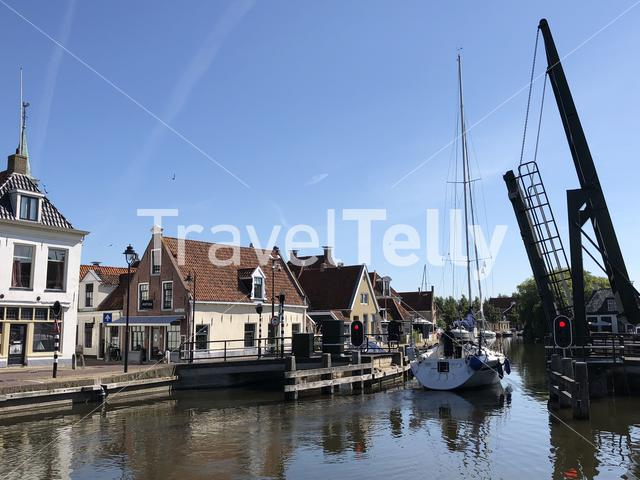 Sailboat sailing through a bridge in the old town of Makkum, Friesland, The Netherlands