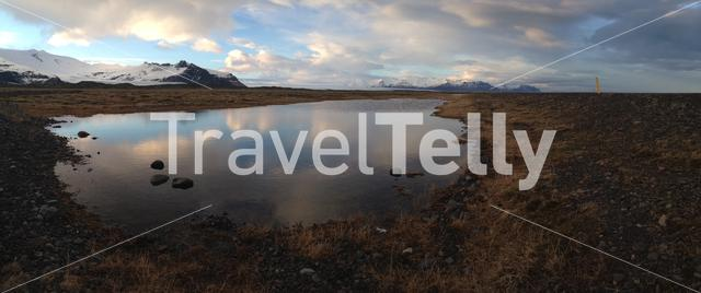 Iceland landscape Panorama with a snowy mountain reflection in a pond