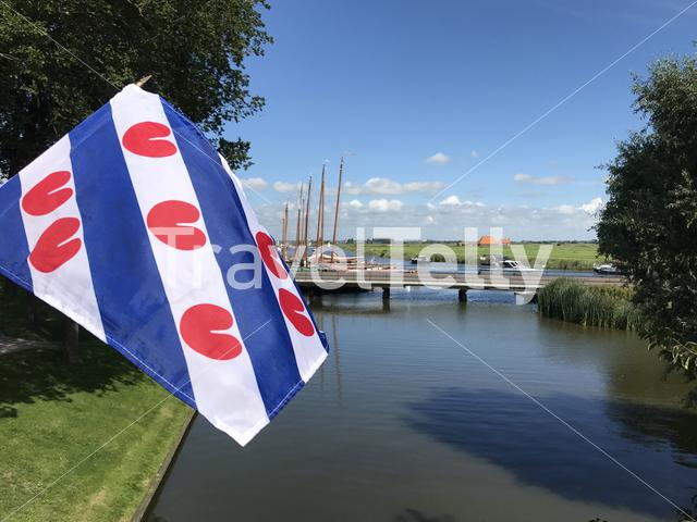 Frisian flag with skutsjes in the background in Sloten, Friesland, The Netherlands