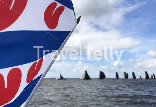 Frisian flag with skutsjesilen in the background in Friesland, The Netherlands