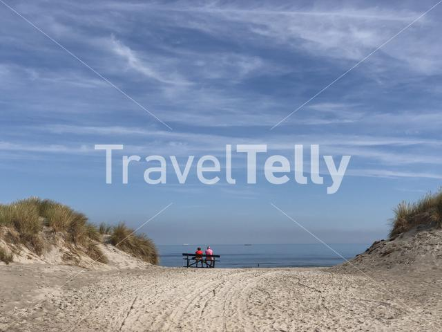 Couple relaxing on a bench at the beach of Ameland island in Friesland The Netherlands