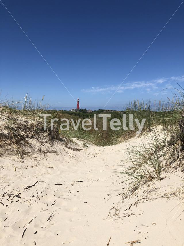 Sand dune with the Lighthouse in the background on Schiermonnikoog in The Netherlands