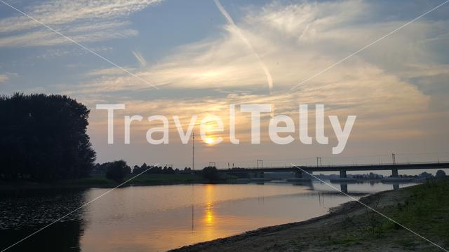 Sunset with reflection in the IJssel river around Deventer in The Netherlands
