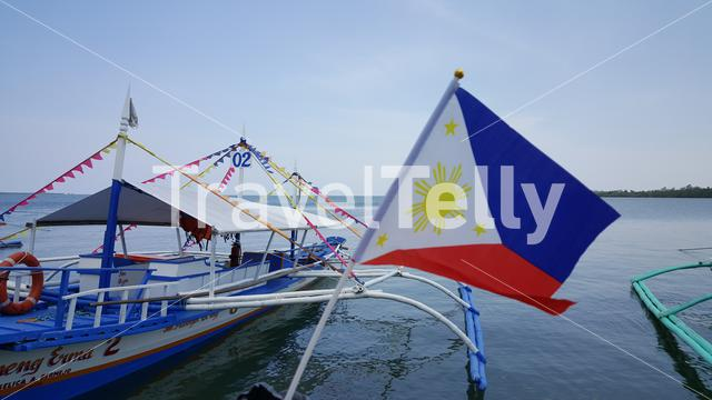 Philipino flag in front of traditional boats at waterfront