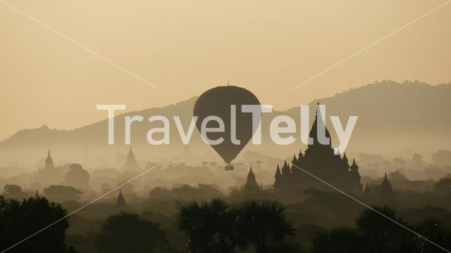 Balloons above the pagodas during sunrise from the Myauk Guni Temple in Bagan Myanmar