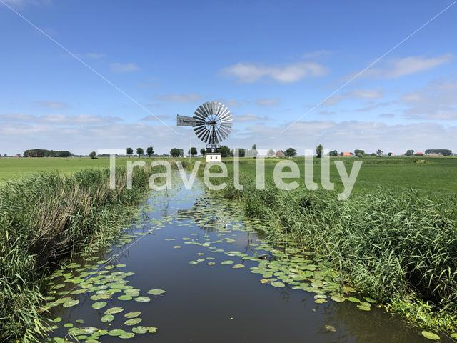 Canal and windmill around the village Boazum in Friesland The Netherlands