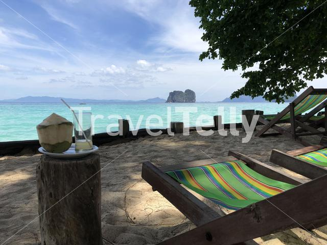 Beach chairs and a coconut near the sea on Koh Ngai in Thailand