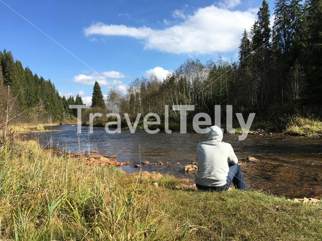Guy sitting on the riverside at Apuseni Natural Park in Romania