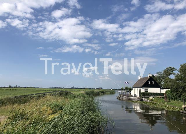 House with a frisian flag next to a lake around Oudega in Friesland, The Netherlands