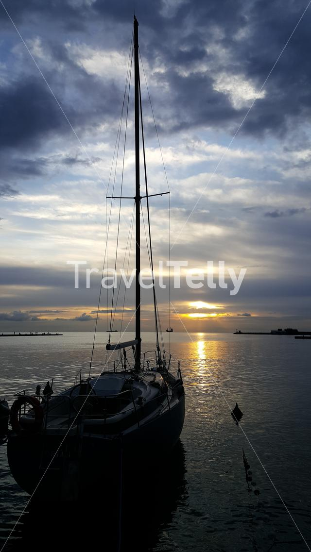 Sailingboat at the pier of Trieste at sunset