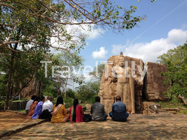 people sitting in front of the Aukana Buddha standing statue of the Buddha near Kekirawa in North Central Sri Lanka