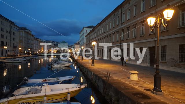 Houses and boats at Ponte Rosso canal in Trieste by night, Italy