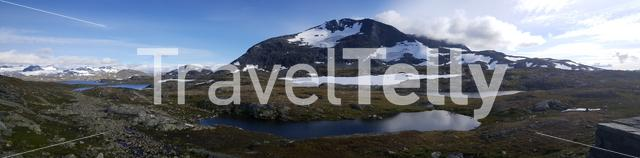 Panorama from a lake in front of the snowy mountains in Jotunheimen National Park Norway