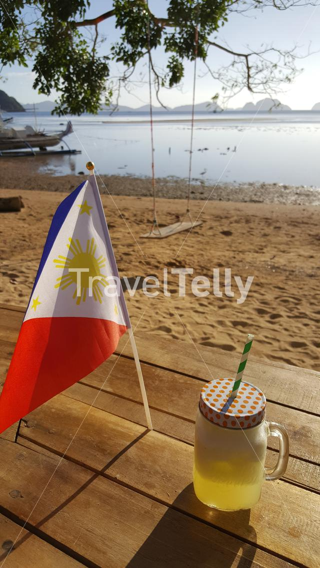 Pineapple juice with national Philipino flag at beach of El Nido
