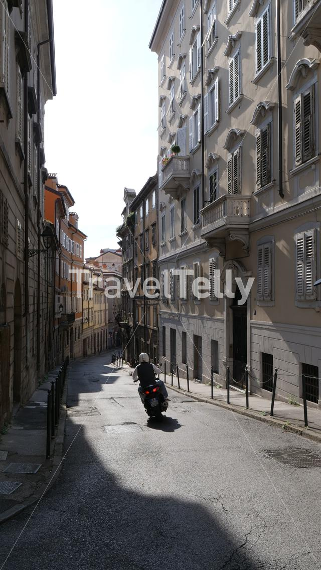 Small alley with high rise buildings and Italian scooter in Trieste, Italy