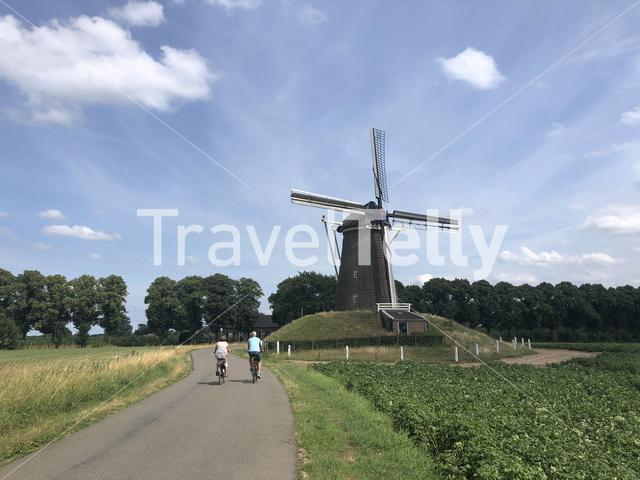 Tourists on a bicycle passing by a windmill in The Netherlands