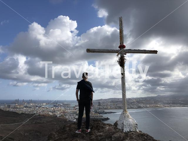 Guy standing next to the cross on top of the hill at La Isleta looking over Las Palmas, Gran Canaria