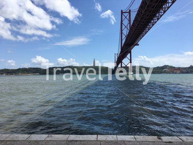 The Ponte 25 de Abril bridge in Lisbon, Portugal, with a view over the Tagus river and the Sanctuary of Christ the King in the distance.