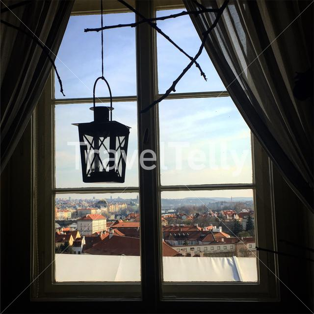 An old lantern with a view of Prague from a window