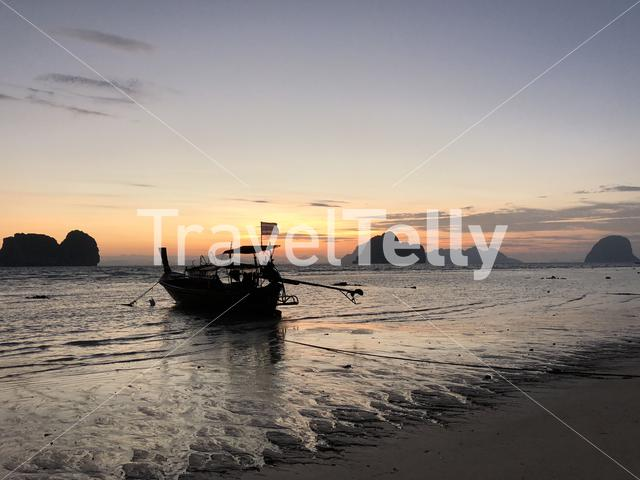 Long-tail boat during sunrise and low tide on Koh Ngai in Thailand