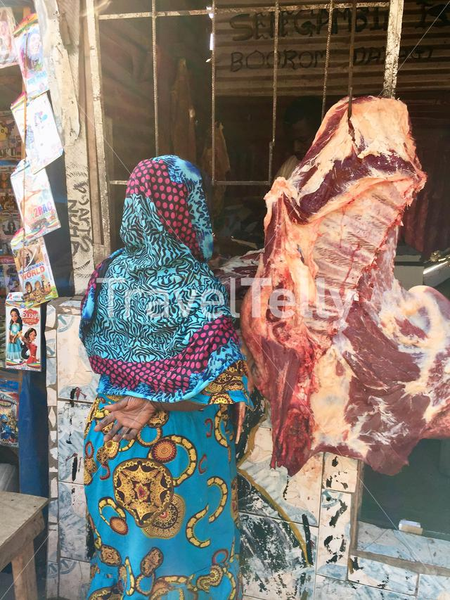 Woman in blue at the butcher's shop in Banjul