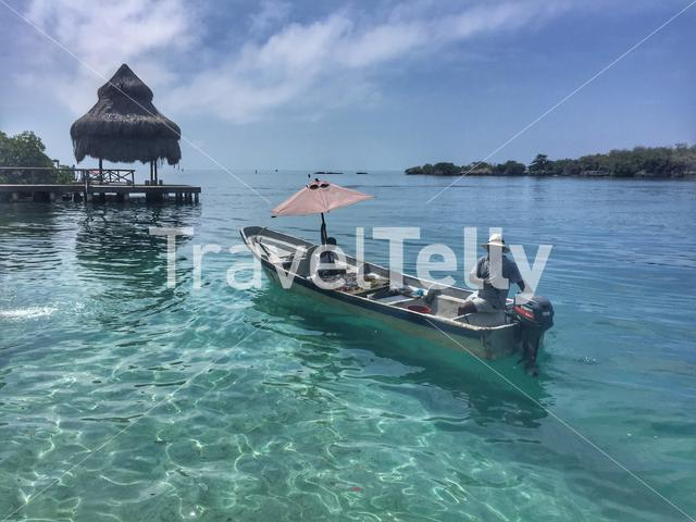 Boat with locals in the clear blue sea of Isla Granda Island in Colombia