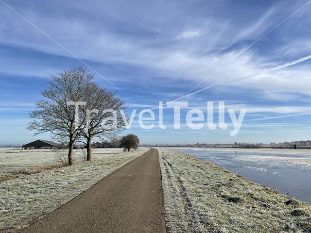Road next to a canal during a winter day in Friesland The Netherlands