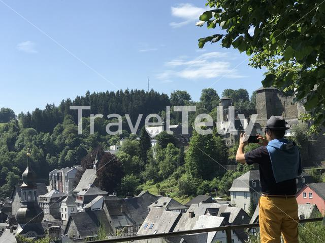 Asian tourist taking a picture with his phone in Monschau Germany