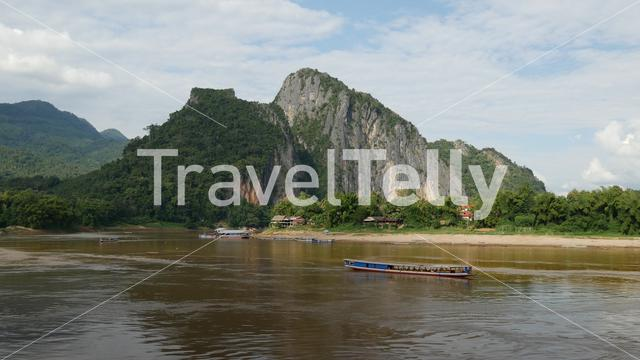 Mountain across the Pak Ou Caves with longtail boat passing by, Laos