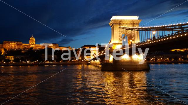 The Széchenyi Chain Bridge is a suspension bridge that spans the River Danube between Buda and Pest sides of Budapest at night