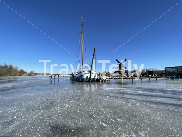 Panorama from people ice skating on a frozen lake with the windmill from IJlst in the background in Friesland The Netherlands