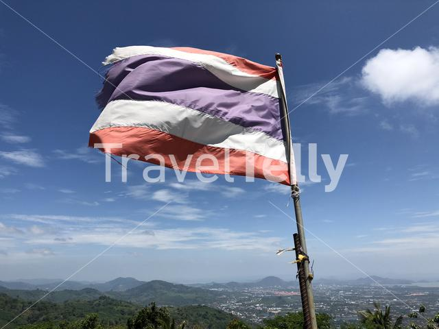 Thai flag next to the Golden buddha statue in Phuket, Thailand