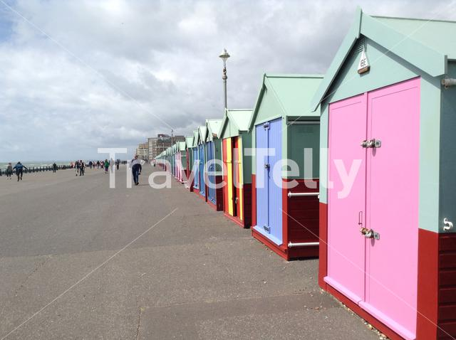 Colourful beach huts lining seafront in Brighton England